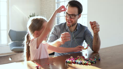 Caring father helping little child daughter stringing necklace of beads Caring young father teaching helping cute little child girl stringing necklace of colorful beads, happy parent dad and small kid daughter enjoy creative leisure hobby at table spend weekend at home craft stock videos & royalty-free footage