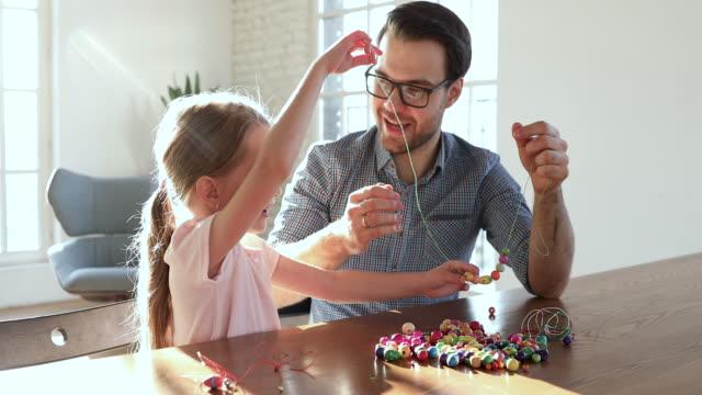 關心父親説明小女兒串項鍊的珠子 - 手工藝 個影片檔及 b 捲影像