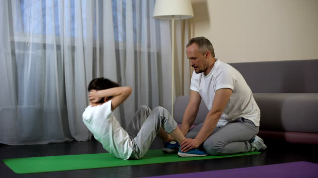 Caring father holding his sons legs while doing crunches, sport lifestyle video