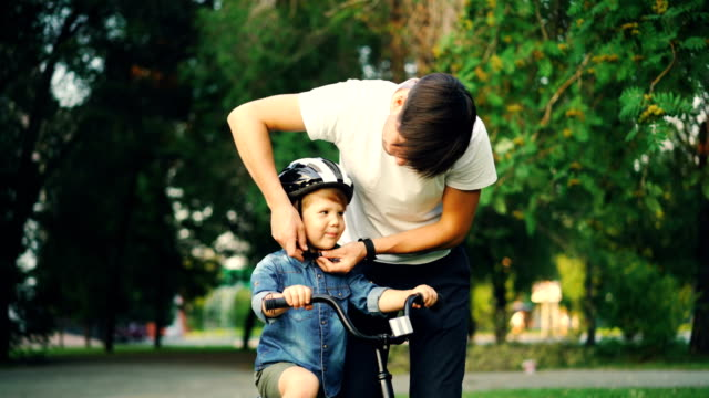 Caring father is putting safety helmet on his little son's head then teaching happy boy to ride bicycle while loving mother is watching them and smiling.