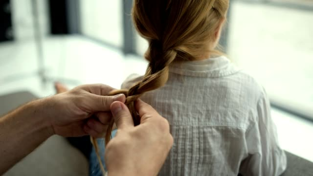 Caring father plaiting hair of his daughter at home video