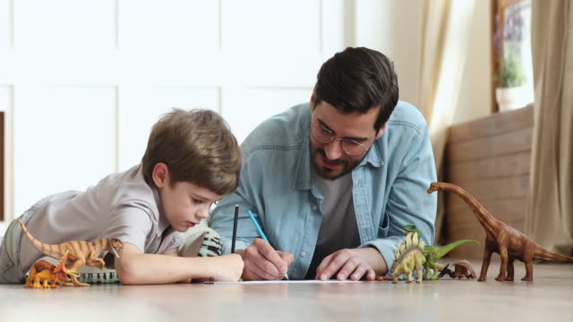 Caring father playing with child son drawing lying on floor