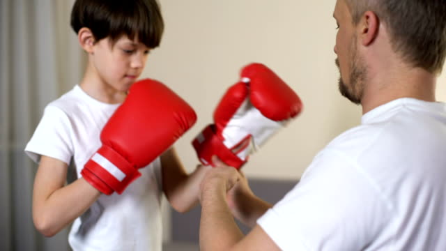 vídeos de stock, filmes e b-roll de pai carinhoso, calçar luvas de boxe de braços filho e ensinando a se defender - artes marciais