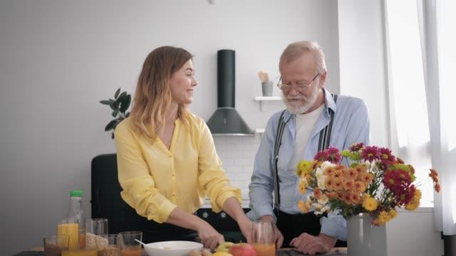 vídeos y material grabado en eventos de stock de cuidando a la generación mayor, alegre sonriente con su abuelo peppy divertirse hablando y preparando un desayuno saludable para mantenerse saludable en la cocina en la mesa - árboles genealógicos