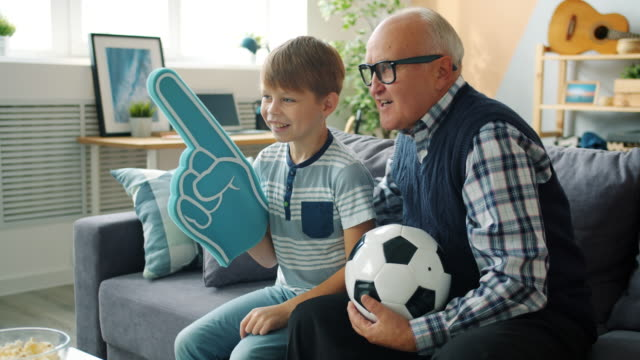 Caring grandad and happy boy watching football on TV holding foam hand and ball Caring grandad and happy boy are watching football on TV holding foam hand and ball cheering feeling excited. Happiness, family and childhood concept. match sport stock videos & royalty-free footage
