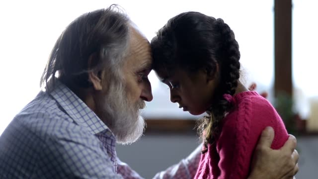 Caring grandfather consoling his little sad girl video