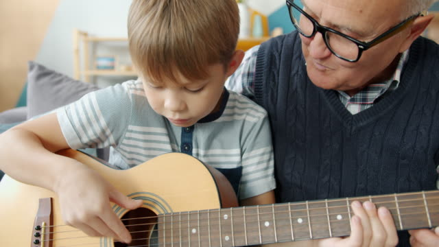 Caring grandfather helping cute kid teaching guitar playing at home together