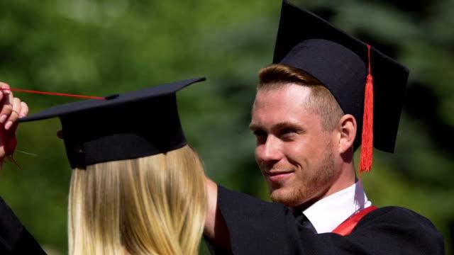 Caring male graduate adjusting tassels on girlfriend's cap, couple in love video