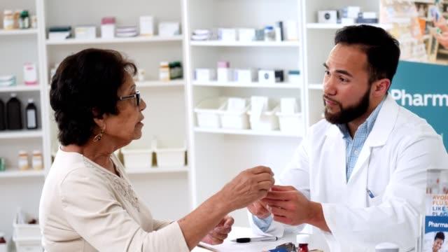 caring male pharmacist reviews senior customer's prescription - prescrizione medica video stock e b–roll