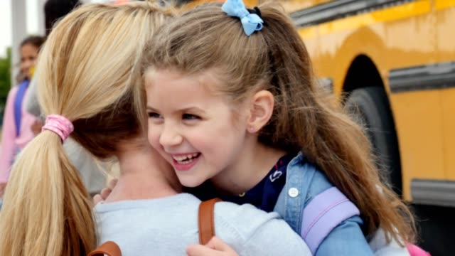 caring mom hugs daughter before the girl boards school bus for her first day of kindergarten - genitori video stock e b–roll