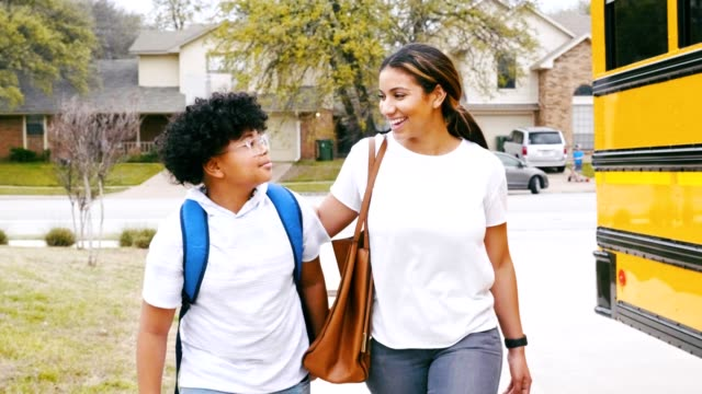 vídeos y material grabado en eventos de stock de cuidar mamá camina hijo a la parada de autobús de la escuela - autobuses escolares