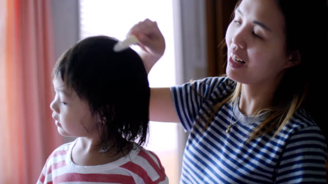 Caring mother combing daughter hair