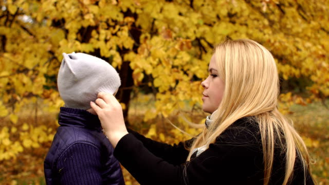 Caring mother corrects hat to child in autumn park video