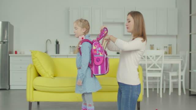 şefkatli anne evde kız öğrenci ve sırt çantası ambalaj - sırt çantası stok videoları ve detay görüntü çekimi