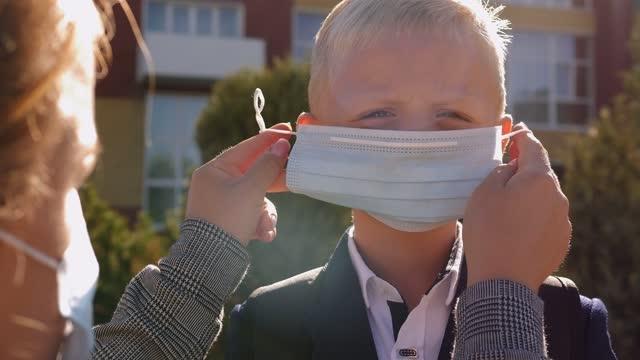 vídeos de stock, filmes e b-roll de uma mãe carinhosa coloca uma máscara médica protetora no filho de um estudante perto da escola. - ucrânia