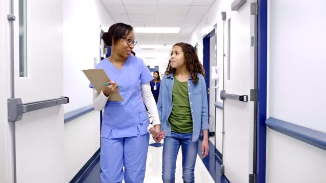 caring nurse walks hand-in-hand with preteen patient in a hospital hallway - inserviente medico video stock e b–roll