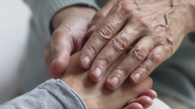 caring old senior adult woman holding young female hands, closeup - nipote femmina video stock e b–roll