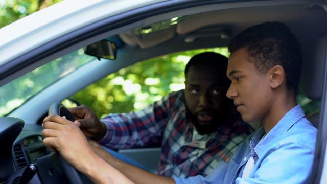 stockvideo's en b-roll-footage met zorgzaam ouder onderwijs zoon hoe te rijden auto, tijd samen doorbrengen, familie - onderwijzen