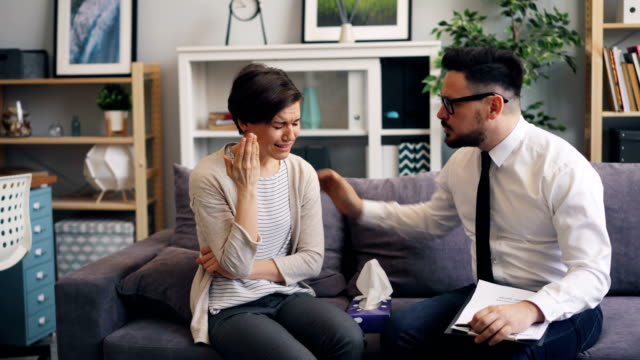 Caring psychologist helping crying woman giving paper tissue touching shoulder