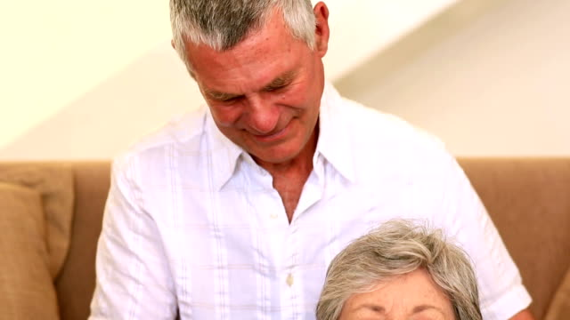 Caring senior man giving his wife a shoulder rub video