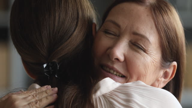 Caring senior mother hugging adult daughter with eyes closed, closeup Caring senior mature beautiful mom hugging adult grown young daughter enjoying cuddling embracing with eyes closed, two generations women family reunion and sweet tender mothers love concept, closeup granddaughter stock videos & royalty-free footage