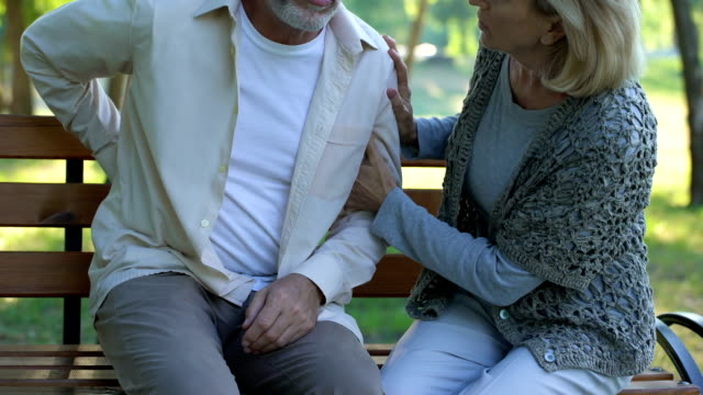 Caring wife calming her old husband, problems with lower back, pinched nerves Caring wife calming her old husband, problems with lower back, pinched nerves pinching stock videos & royalty-free footage