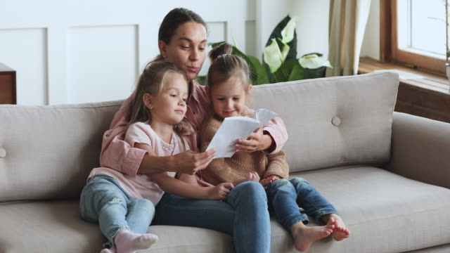 Caring young mother reading book hug cute children daughters