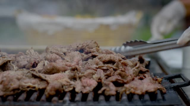 Carne Asada cooking on the grill Close up of carne asada being cooked on an outside charcoal grill in Chicano Park, San Diego. pork stock videos & royalty-free footage