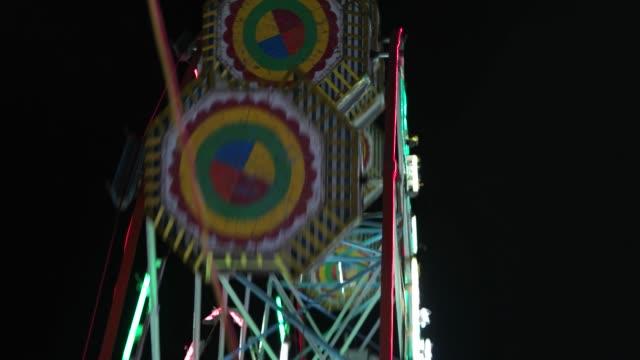 carnival med pariserhjul, ljusa färgglada lampor, bil karusell på natt närbild - wheel black background bildbanksvideor och videomaterial från bakom kulisserna