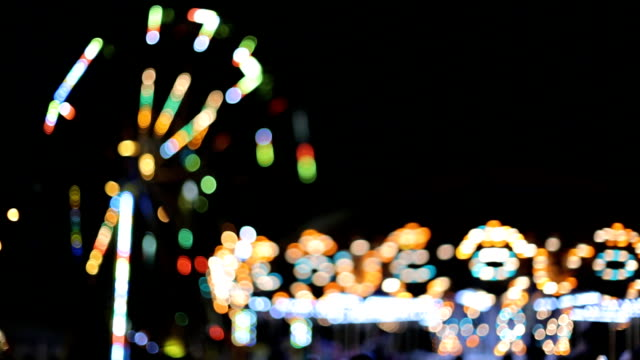 Carousel lights in amusement park at night out of focus video