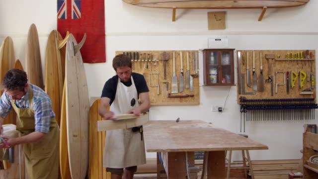 carpenter and apprentice make surfboards shot on red camera - modella negozio video stock e b–roll