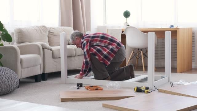 Carpenter assembling table at home
