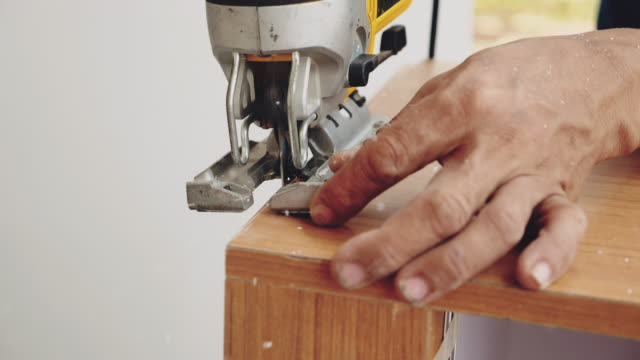 Carpenter at Work in Carpentry Workshop Carpenter using a jigsaw to cut a piece of wood in his shop cabinet stock videos & royalty-free footage