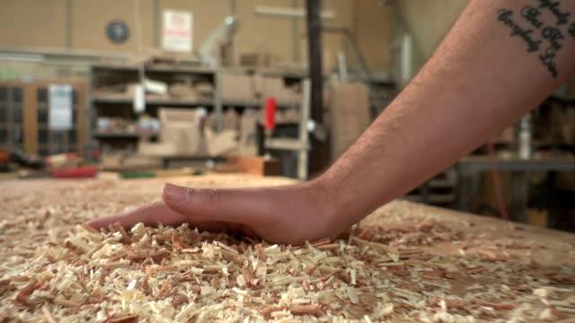 carpenter  brusing off wood shavings - segatura video stock e b–roll