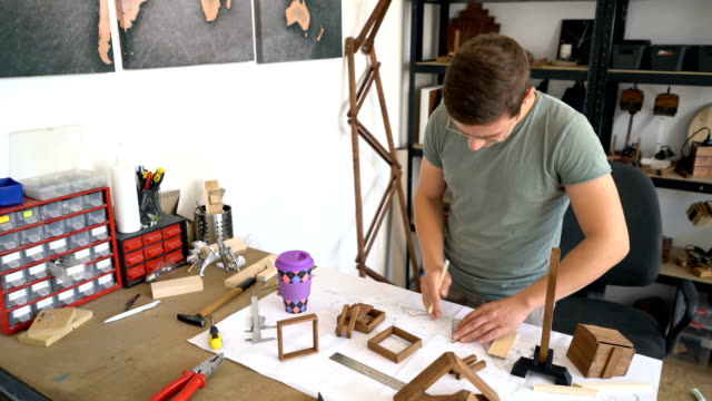 Carpenter building wooden product in his workshop video