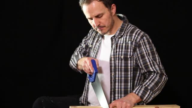 Carpenter carefully sawing wood video