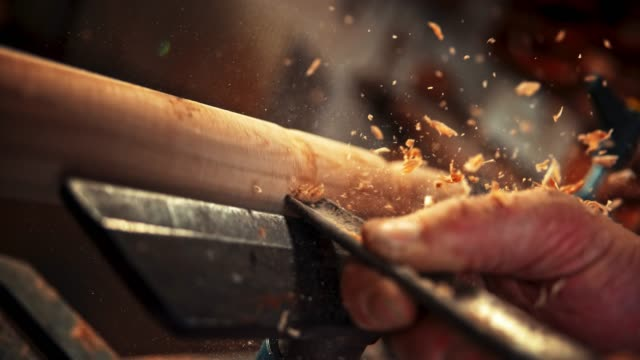 SLO MO Carpenter chiseling a rotating piece of wood and particles are flying around
