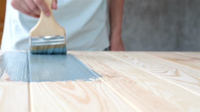 Carpenter covers the wooden surface with blue paint. video