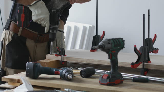 Carpenter drilling hole in plywood boards video