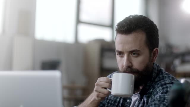 Carpinteiro, bebendo café e usando o laptop na oficina - vídeo