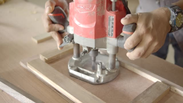 carpenter during working at wood workshop. Man carpenter working at a work bench with power tools,steel tape for measure dimension of work pieces,push plywood to electric saw blade.4k dci slow motion power tool stock videos & royalty-free footage