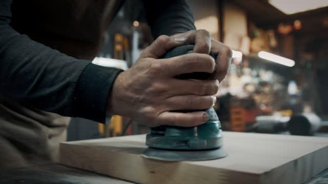 un falegname macina un pezzo di legno per una sedia in stile loft. da vicino. - carta vetrata video stock e b–roll