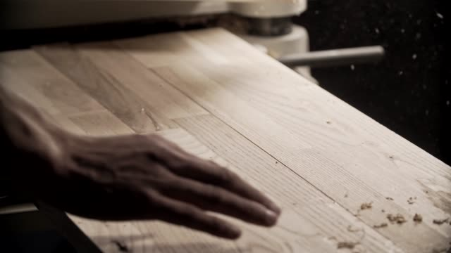carpenter hand touches wooden board. master hand blows away dust from boards - segatura video stock e b–roll