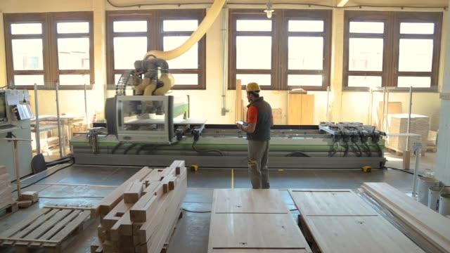 vídeos de stock, filmes e b-roll de carpinteiro na fábrica de madeira, usando uma tabuleta digital, verific resultados da máquina de serra circular na fábrica da mobília, equipamento de segurança desgastando - mobília