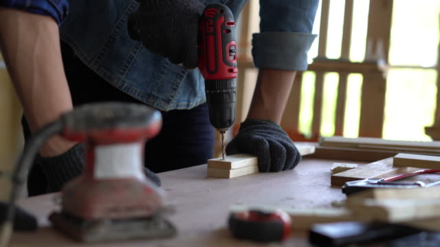 carpenter is drilling the wood