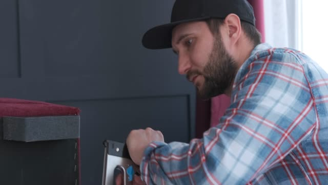 Carpenter is fixing details by furniture stapling machine