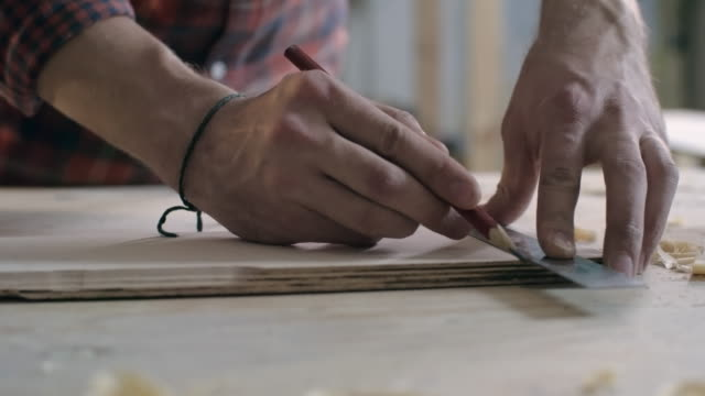 Carpenter marking wood plank video