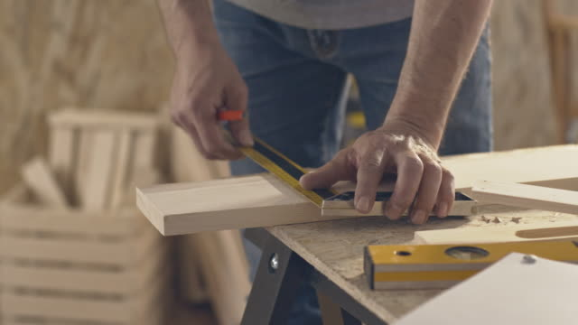 Carpenter marking wooden plank, using pencil and ruler Carpenter marking wooden plank, using pencil and ruler. carpenter stock videos & royalty-free footage