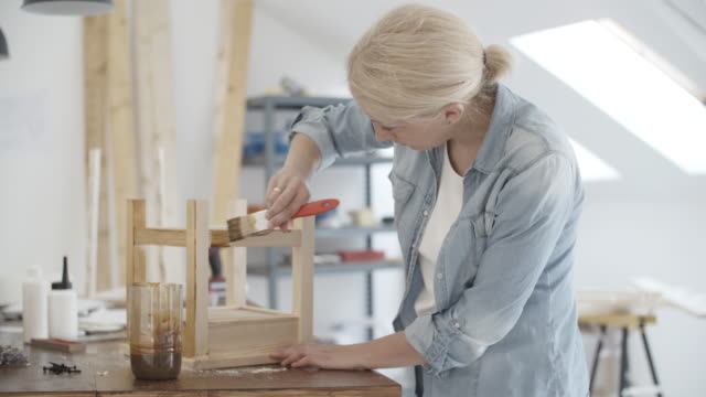 4 k: carpenter gemälde möbel in ihren workshop. - tischlerarbeit stock-videos und b-roll-filmmaterial