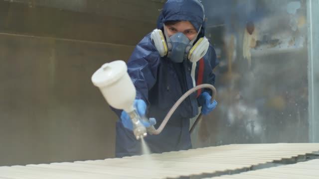 Carpenter Painting Planks in Workshop